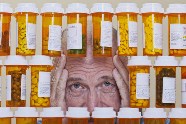 Depressed Senior Man Looking Through Rows of Prescription Medica